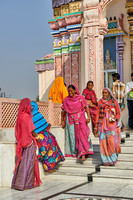 Women in colorful saris in front typical colorful temple