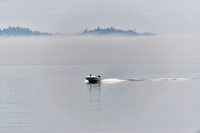 motorboat driving through the fog of Johnstone Strait|