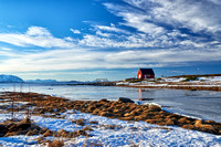 winter landscape with typical red house at Senja shore