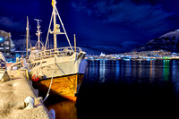night shot of a snow covered vessel in harbor of Tromsø