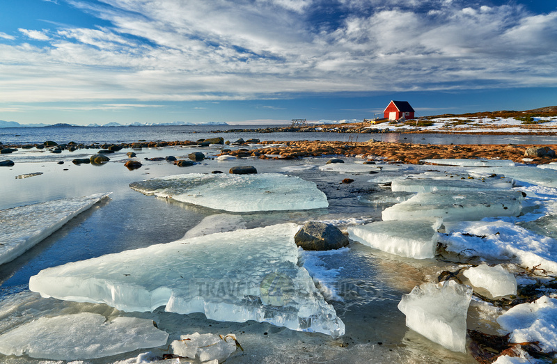 winter landscape with ice floes and typical red house