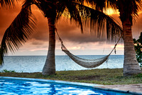 Hammock in front of palm trees, sea and sunset