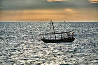 dhow swings in sea at sunset